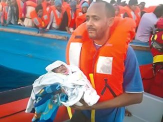 A man carries his 5-day-old son after being rescued from a crowded wooden vessel in the Mediterranean Sea. The pair were fleeing from Libya. PHOTO: CNN