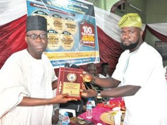 The chairman on the occasion and member of the Senate representing Oyo South Senatorial District, Rilwan Akanbi (left), presenting a plaque to a staff member of the Nigerian Tribune, Alhaji Nurudeen Alimi, for the conferment of a merit award on the newspaper by the Ahmadiyya Movement in Islam, Nigeria, Ibadan Mission, at a ceremony held to commemorate the 100 years of the Movement in Nigeria, in Ibadan, last weekend. PHOTO: D'TOYIN.