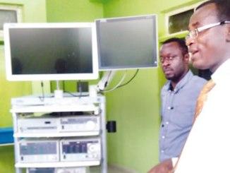 Dr Olawale Olakulehin (right), explaining the use of the minimal invasive surgery machine.