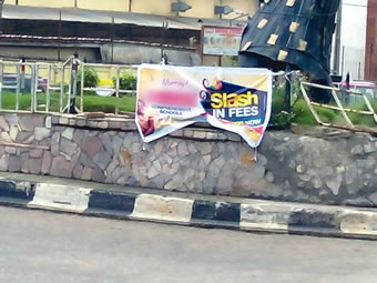 A roadside banner 'enticing parents with slash in fees