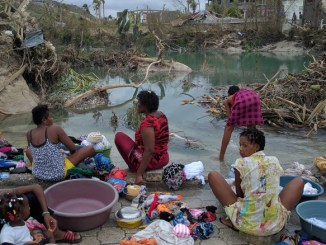 Women and children wash clothes in the aftermath of the devastating hurricane. PHOTO: CNN
