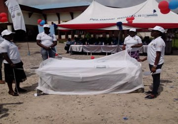 Health workers demonstrating how to set up a treated mosquito net. Photo: Ebenezer Adorokiya.