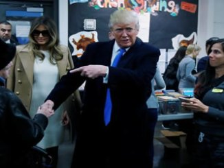 Republican presidential nominee Donald Trump shakes hands with a woman before voting at PS 59 in New York, New York, US, on Tuesday. REUTERS.