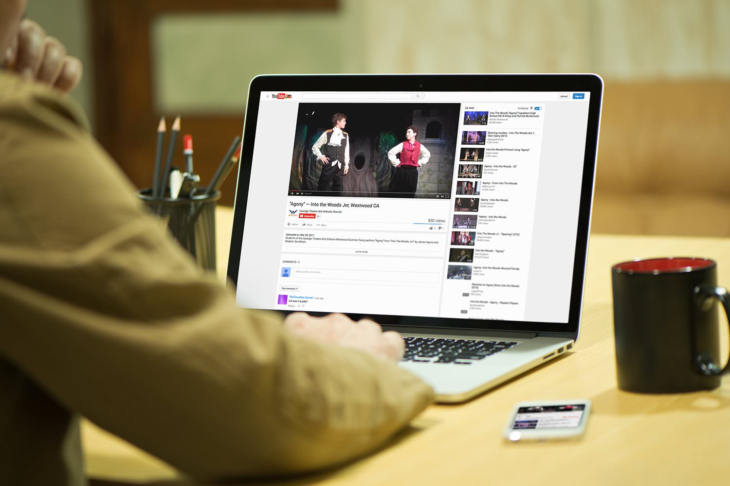 A man views a video from the Upstage YouTube channel on a laptop – Tribus Creative – brand communications for small business