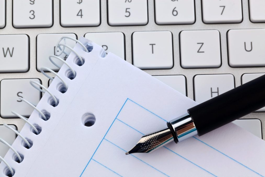 a notepad and keyboard of a computer. write down and save.