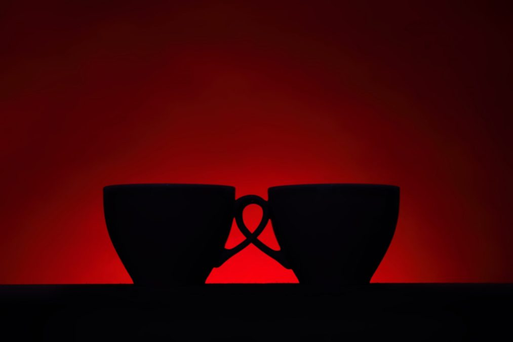 Silhouettes of two coffee cups on red background