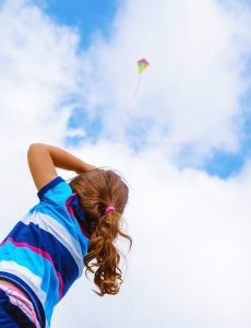 Little girl looking up in the sky on beautiful colorful air kite