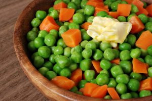 Bowl of freshly steamed peas and carrots with butter on wood bac