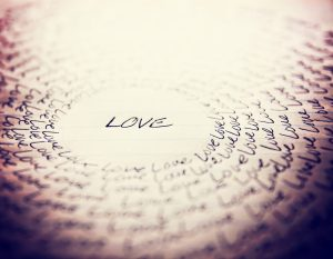 the word love written on a lined piece of school paper in ink wi