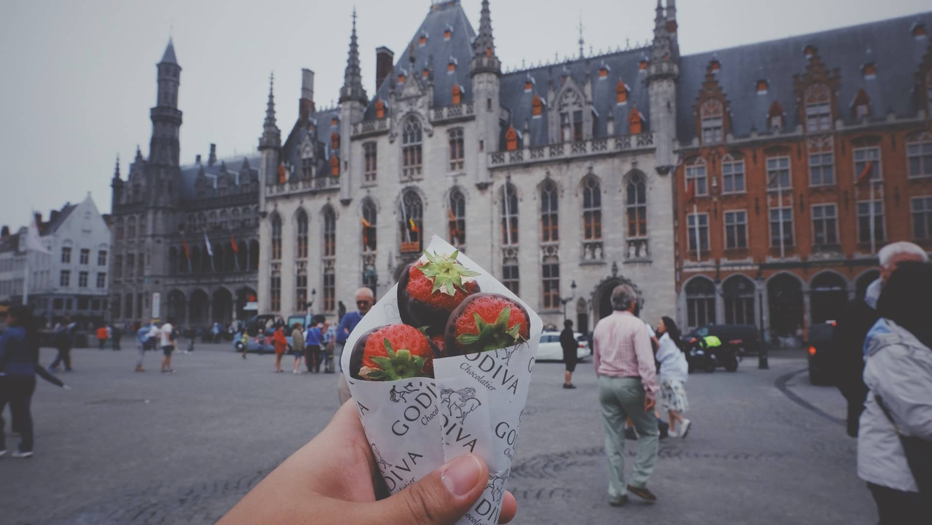 Cup of strawberries and chocolate with historical buildings of Belgium in the backgound on a grey day