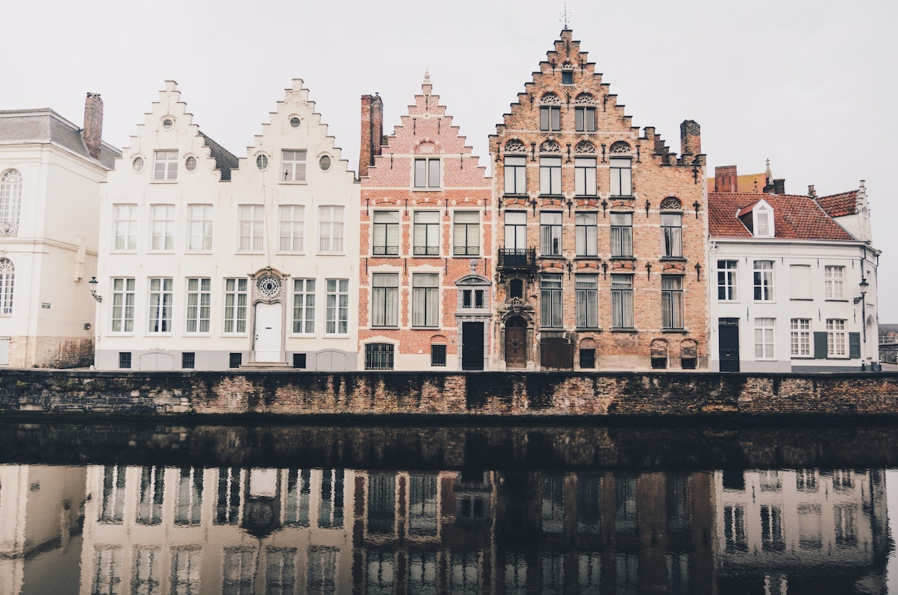 authentic red and white brick houses with their reflection on the water in Belgium