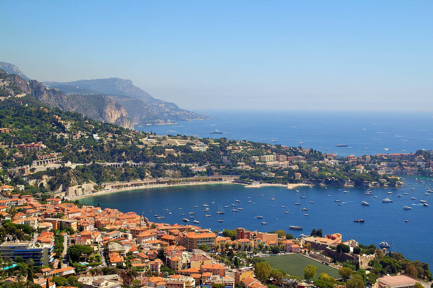 Bay of Nice, France with red roof houses, a sandy beach, and clear blue water with lots of boats