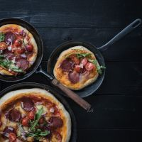 köstliche pan pizza mit ungarischer pick salami, mozzarella, rucola, kirschtomaten, roten zwiebeln, pecorino und einem kalt gegangenen hefeteig, der die pizzaparty perfekt macht!