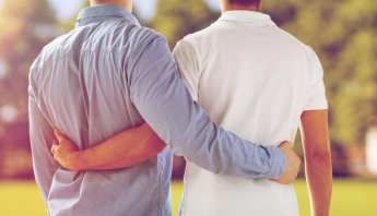 Gay couple tenderly embracing while looking ahead