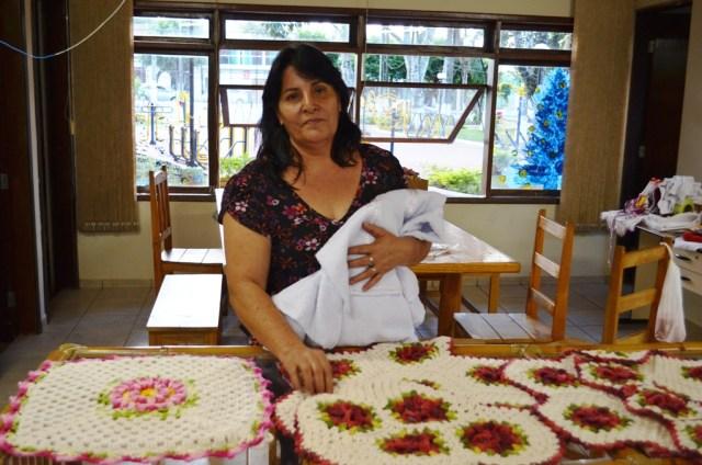 Dona Ines mostrando alguns dos trabalhos em crochê.