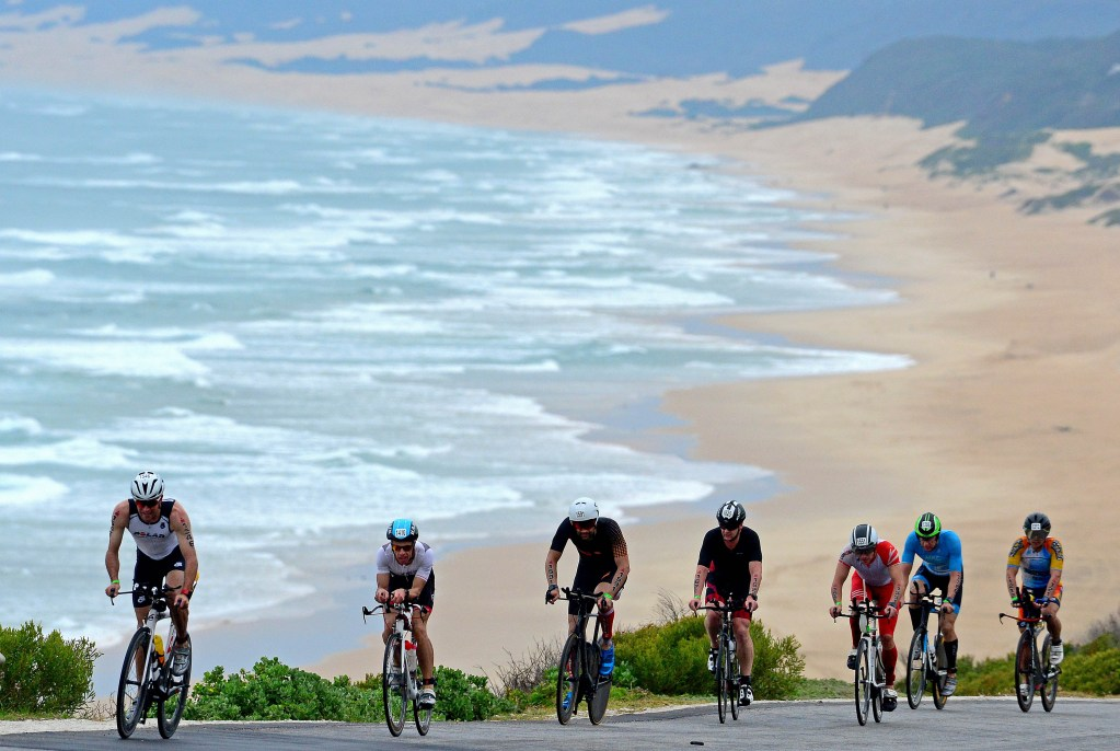 PORT ELIZABETH - SEPTEMBER 2:   General view of age group triathletes climbing a hill with the beach and dunes behind them during the Isuzu IRONMAN 70.3 World Championship Men in Port Elizabeth, South Africa on September 2, 2018. Over 4,500 athletes from over 100 countries will be represented in this years 70.3 World Championship. (Photo by Donald Miralle/Getty Images for IRONMAN).