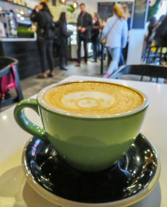 my lavender latte in green coffee cup at Bibble and Sip in New York City