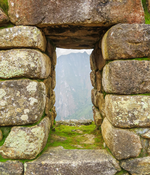 looking through one of the many stone windows in machu picchu peru