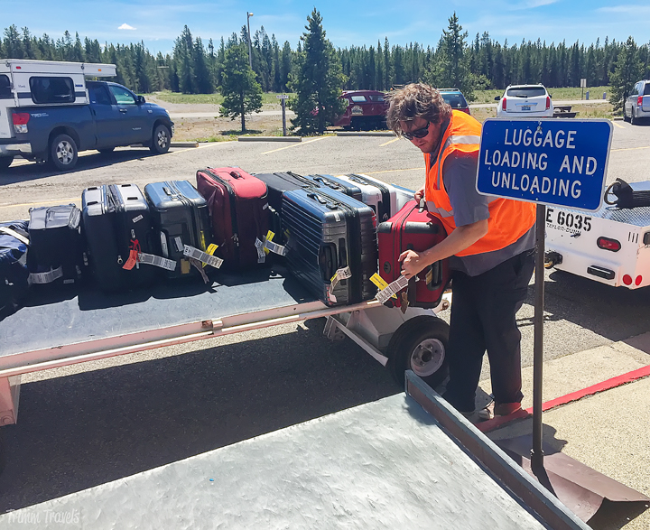 airport employee loading bags outside the airport at the curb-best time to visit yellowstone