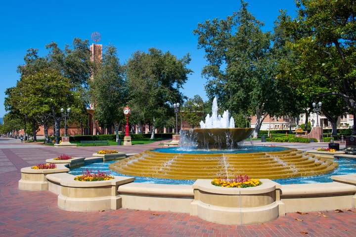 Circular water fountain flanked by colorful flowers and red brick walkways at University of Southern California