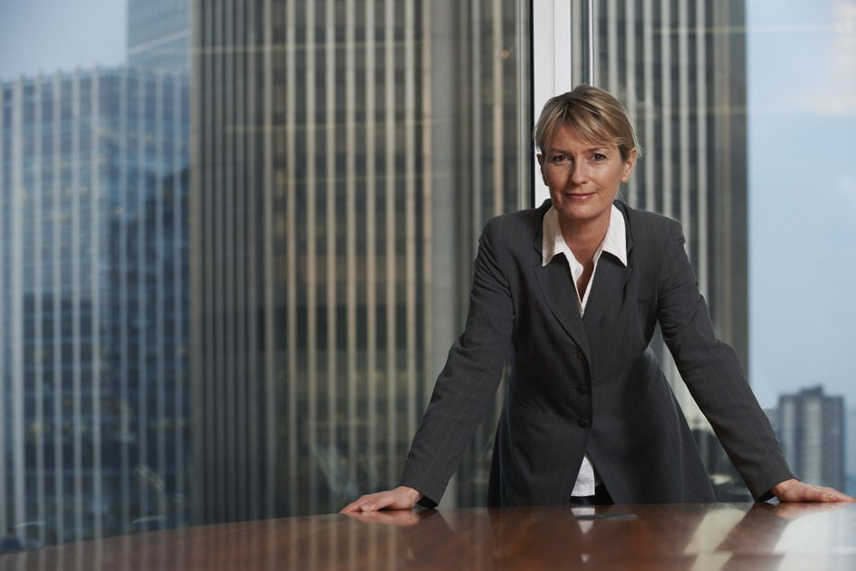 Business woman leaning on chair in boardroom looking at camera
