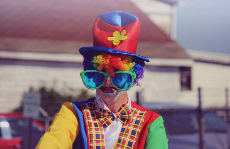 Clown face with multi colored hat and ite