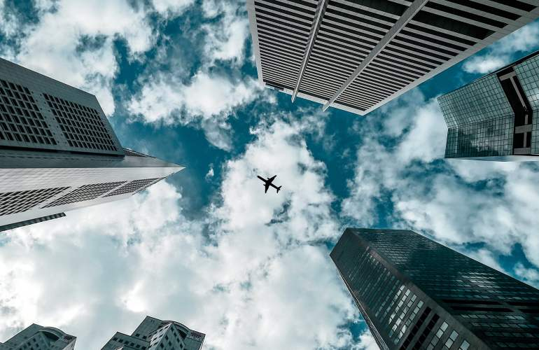 Air plane flying over tall buildings.