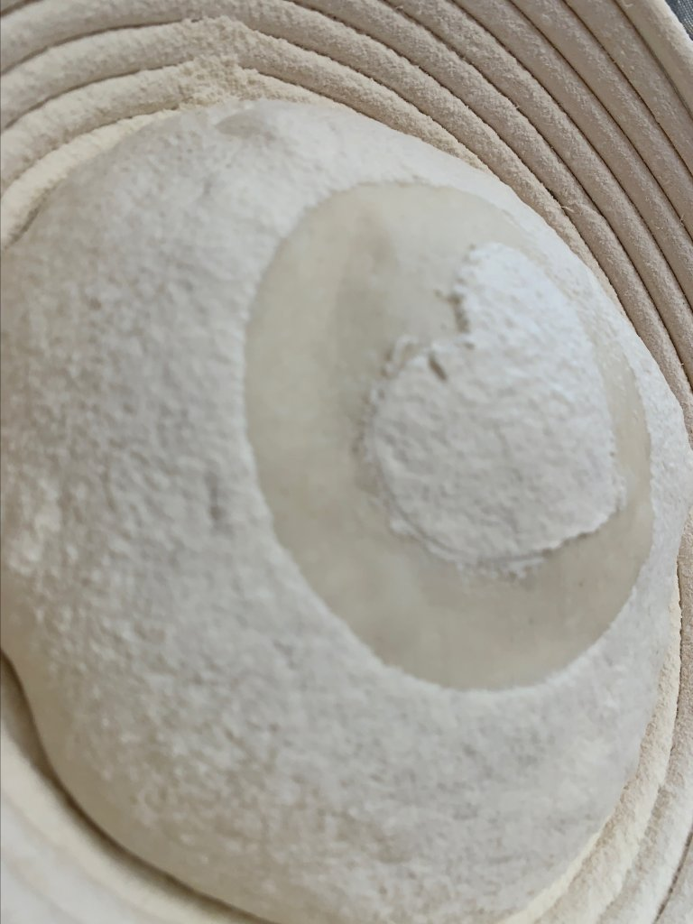 Bread dough dusted with flour in the shape of a heart.