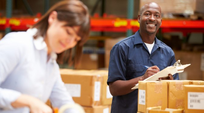 Man smiling with packaging supplies, and woman taping box