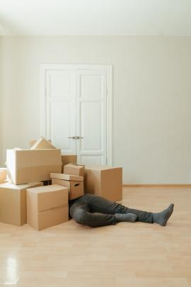 Man laying under boxes