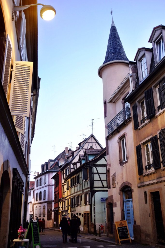 A small street in Strasbourg. On the left side is a building with a small tower attached to it.