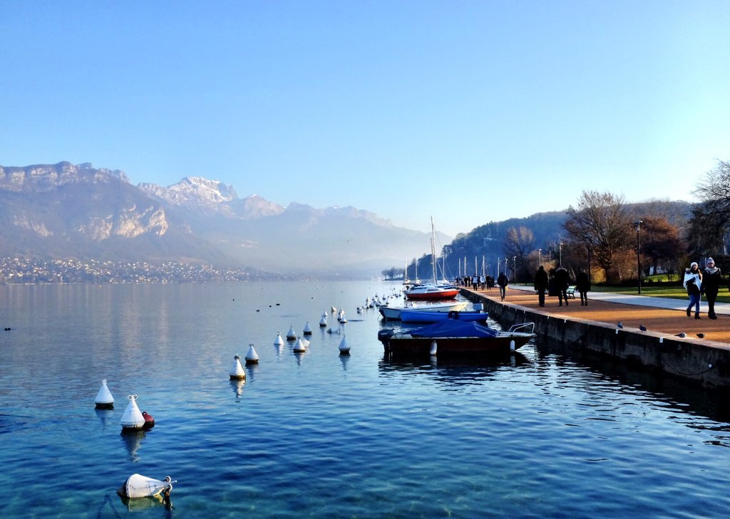 Annecy in winter - view of the lake with boats and mountains in the background