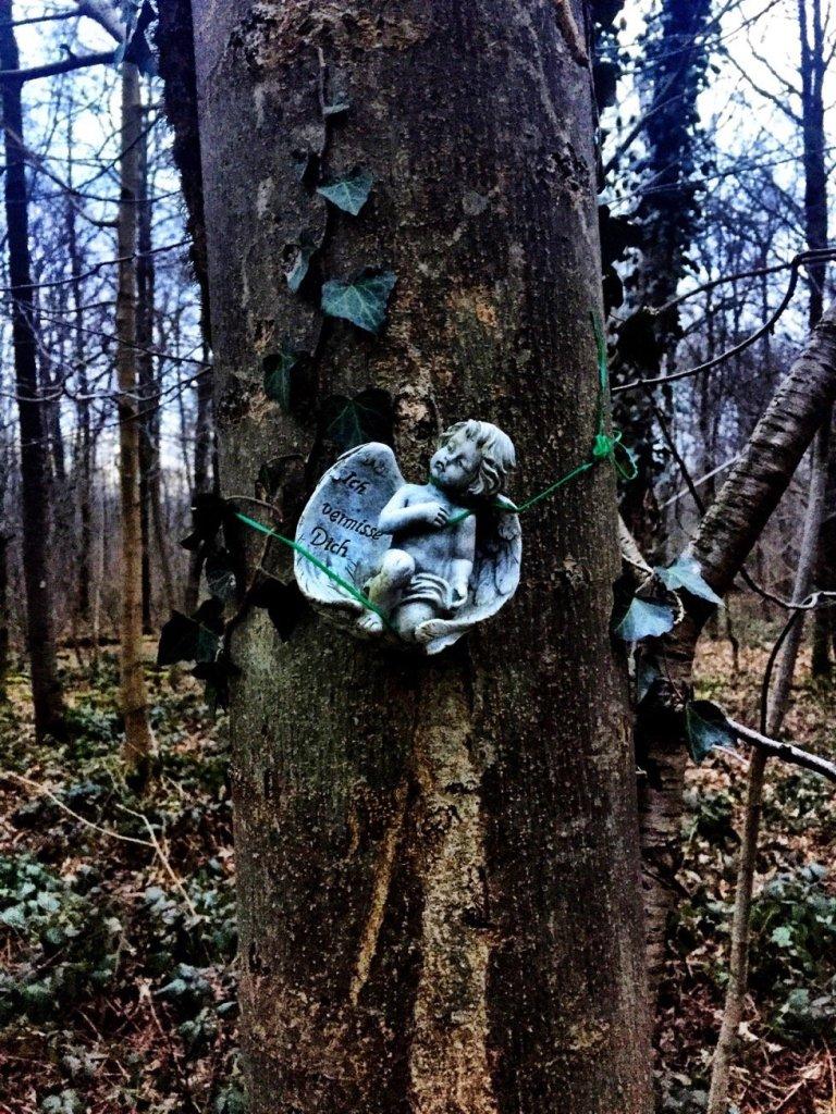 "An angel bound to a tree we saw in a forest in Birsfelden. The text says ""I miss you"""