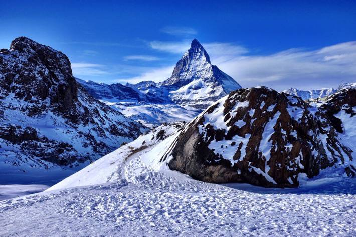 Beautiful picture of the Matterhorn. Around it are a lot of rocks and even more snow. Near Zermatt