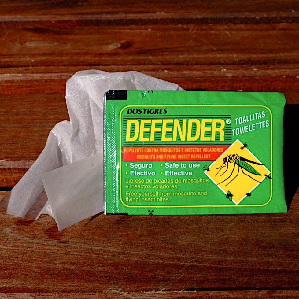 A green pack of Dos Tigres Defender tissues. They contain DEET and are perfect for any occasion where you aren't allowed to have liquids on you. There is also an unpacked tissue on the picture