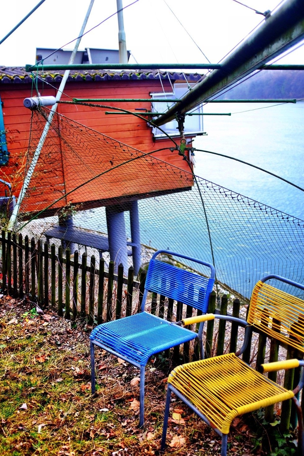 Some colorful chairs in the front of a traditional fishing hut