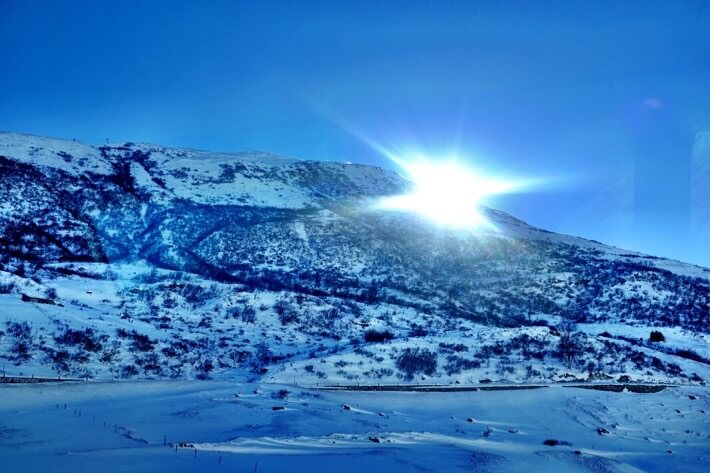 The sun just goes up behind a snow covered mountain. As seen from the Glacier Express