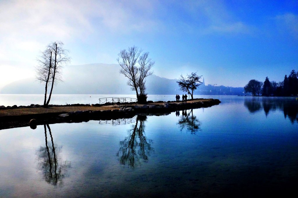 The lake Annecy reflects the trees and the jetty on a beautiful winters day