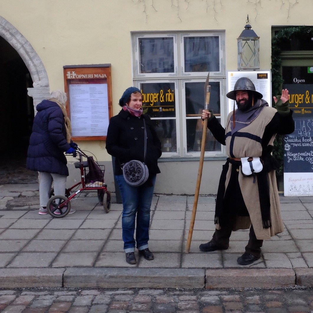 A actor in medieval armour is waving at us in the Old Town of Tallinn