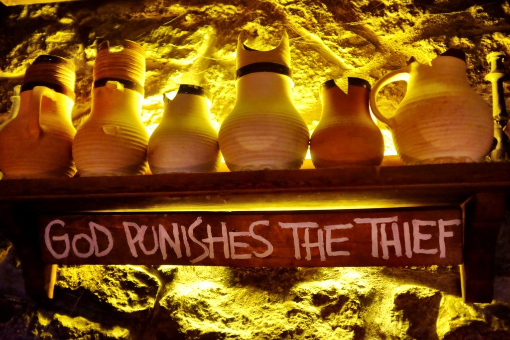 A shelf with some old ceramic mugs with a wooden plate under it which says: God punishes the thief. Found in the Draakon Pub in Tallinn