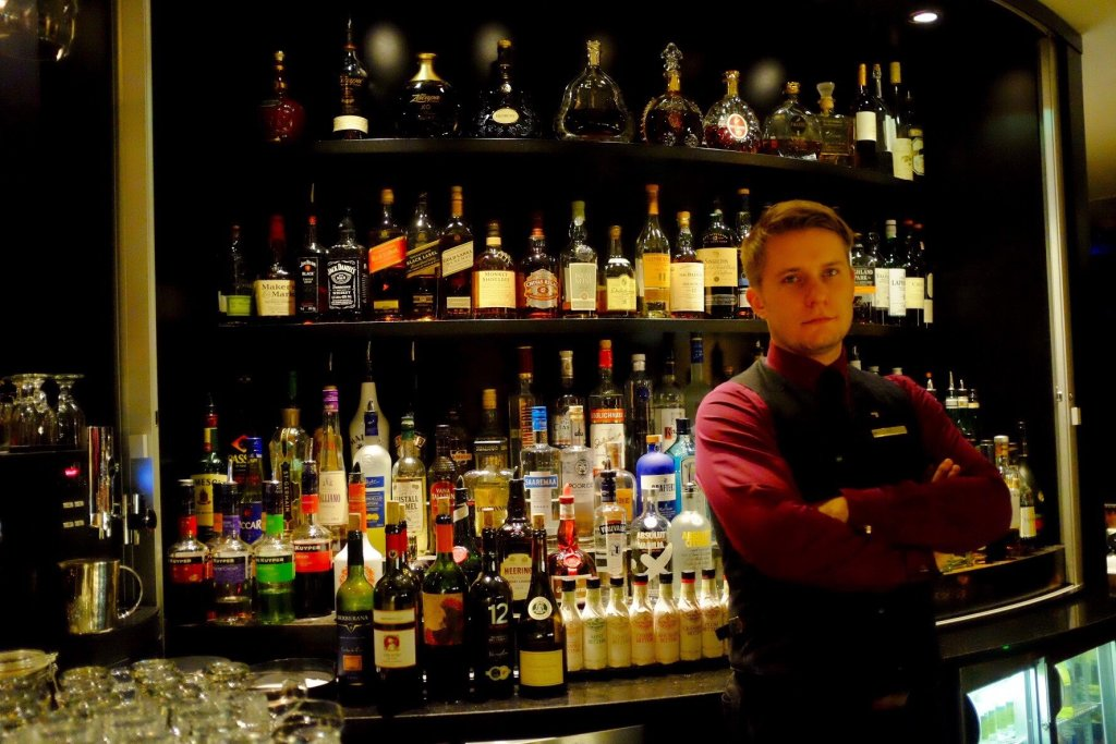 The barkeeper of the Horisont bar in Tallinn posing in front of his bar