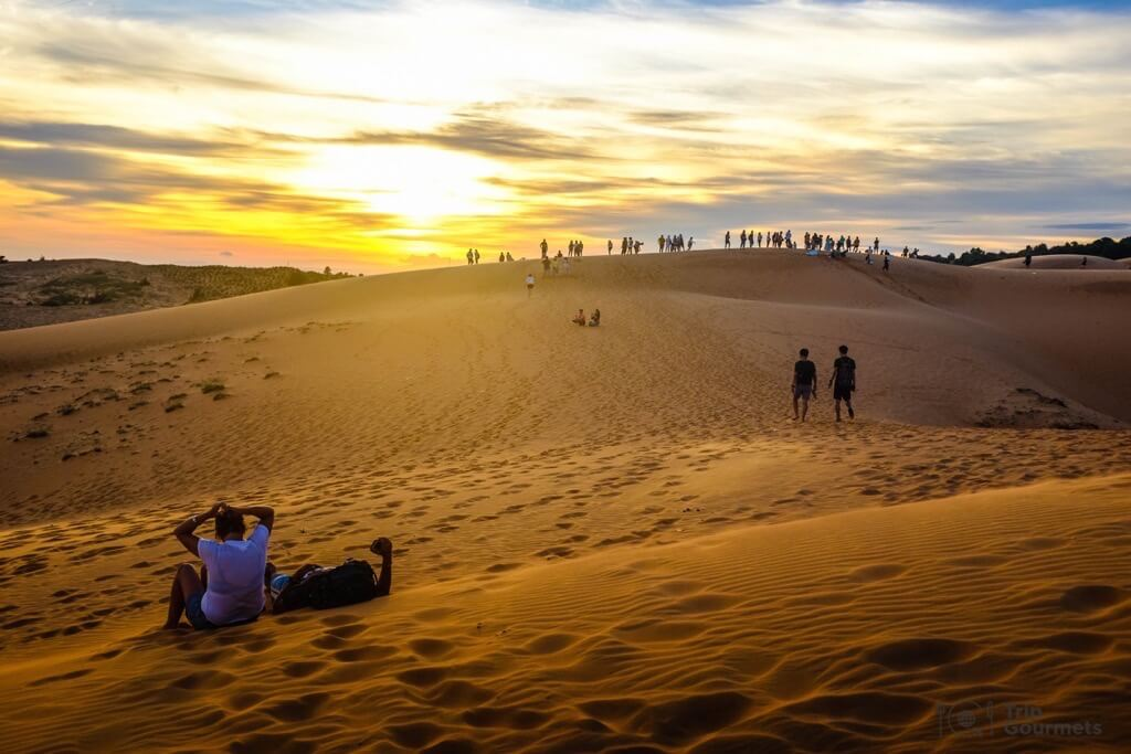 Things to do in Mui Ne Muine red dunes sand sunset clouds people
