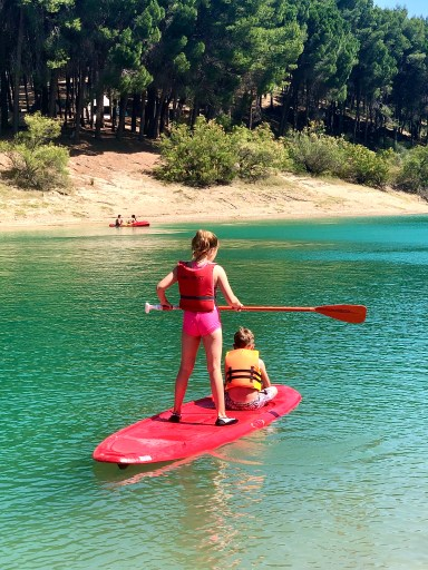 Two children on an SUP paddleboard on a lake in spain, camp ardales