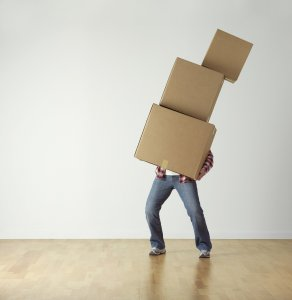 A man carrying three boxes. Lift the boxes properly to avoid injuries while moving.