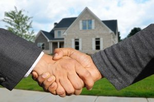 a handshake in front of the house