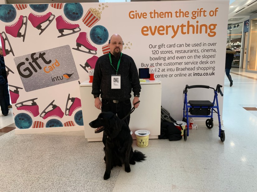 Fraser standing in front of the info stall with his guide dog Mercer.