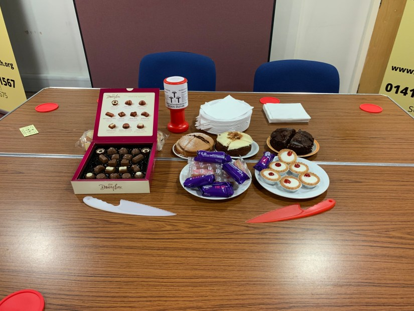 Some lovely cakes and chocolate sweets on a table.