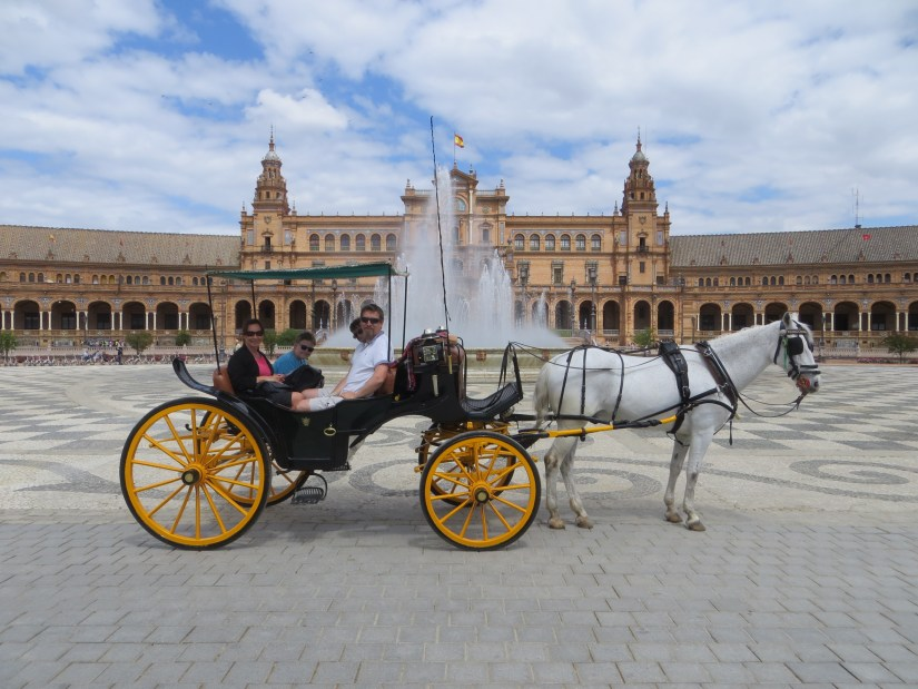 A family are sitting on a Horse-Drawn Carriage in seville