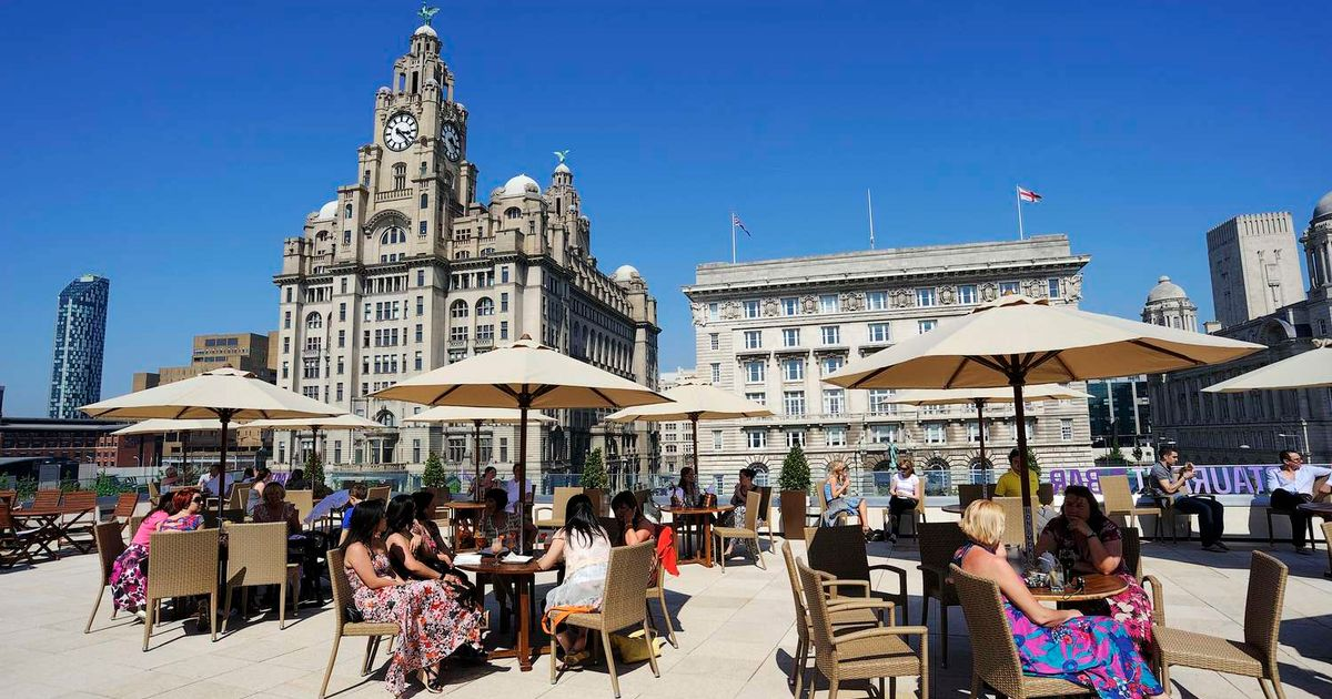 many people are sitting in front of Royal Liver Building Liverpool
