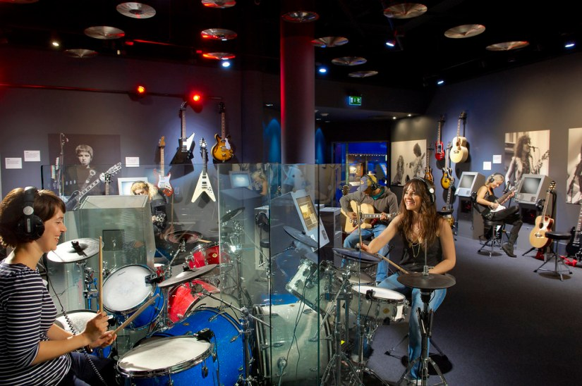 teenagers are playing instrument inside British Music Experience liverpool